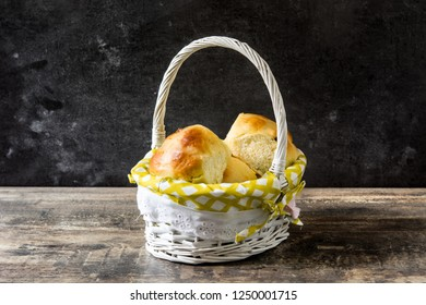 Traditional Easter hot cross buns in a basket on wooden table.