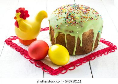 Traditional Easter treats: Easter cake and colorful easter eggs on a white table. Square image