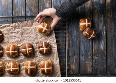 Traditional Easter treats cross buns with raisins and female hands on the grey wooden board. Top view