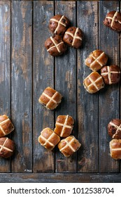 Traditional Easter treats cross buns with raisins on the grey wooden board. Top view