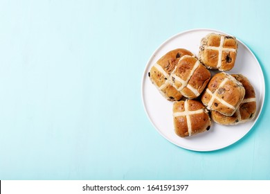 Traditional Easter treats cross buns with raisins over the cyan texture background. Top view