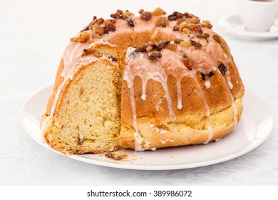 Traditional easter yeast cake covered with white icing and raisins Spongy yeast cake that is traditionally baked for Easter Sunday in Poland, Belarus, Ukraine , Russia. Cup of coffee white background