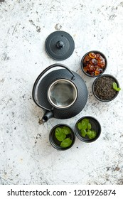 Traditional eastern metal teapot and iron cups with mint tea leafs over the white rusty stone background