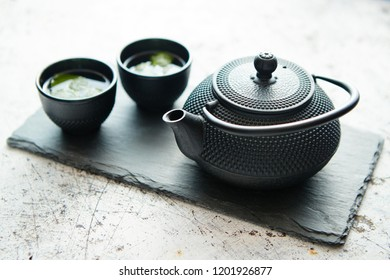 Traditional eastern metal teapot and iron cups with mint tea leafs placed on stone plate. Over the white rusty stone background