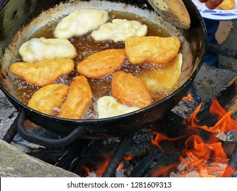 Traditional ecuadorian sweet food - Cheese Empanadas cooked on open fire in big pot with oil