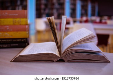 Traditional education learning concept with old textbook in school library with the blurred background of reading area and aisles of bookshelves. For academic education learning concept. Copy Space.