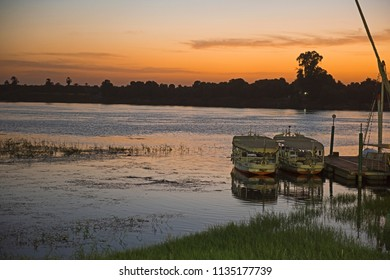 Traditional Egyptian felluca sailing boat on river Nile moored at jetty in dusk sunset