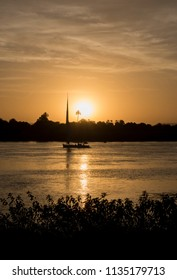 Traditional egyptian felluca sailing boat on river Nile in silhouette at dusk sunset