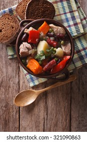 Traditional eintopf soup with meat, sausages and vegetables in the pot on the table. vertical top view