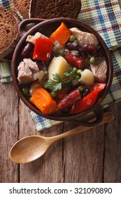 Traditional eintopf soup with meat, sausages and vegetables in the pot close up on the table. vertical top view