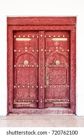 A traditional elaborately carved Arabian house door with brass door knockers and large brass door nails.