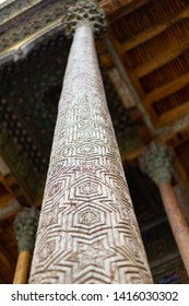 Traditional Elm carving wooden ornamented columns with kokands and ceiling. The wooden pillars support the roof of the iwan. Uzbekistan national traditional islamic architecture elements.