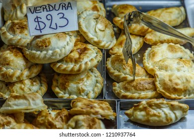 "Traditional empanadas or patty stuffed with vegetables for selling, Buenos Aires, Argentina. Sign ""Verdura"" means ""vegetable""."