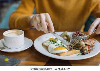 Traditional English breakfast with fried eggs, sausages, beans, mushrooms, and bacon on on a plate and cup of coffee on wooden table.