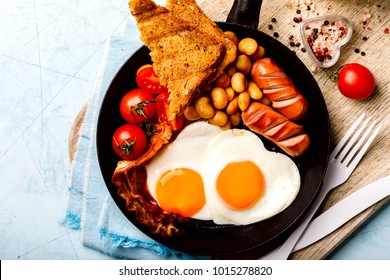 Traditional English Breakfast in the Frying Pan Eggs in the Heart shape. Valentine's Day. Festive Food on the Blue Background.Sausages, Bacon, Beans,Toasts,Coffe and Orange juice