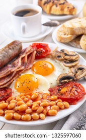 Traditional English Breakfast - plate with fried eggs, sausages, beans, mushrooms and bacon, cup of fresh coffee, croissants and orange juice on white background