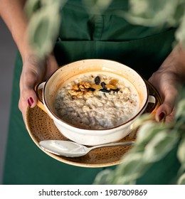 Traditional english breakfast. Woman holds bowl of cereal oatmeal or porridge with milk, raisins and nuts. Close up shot. Soft focus.