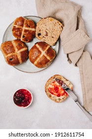 Traditional English Easter Hot Cross Buns on a plate with jam and butter, top view