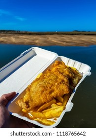 Traditional English fish and chips being eaten by the seaside
