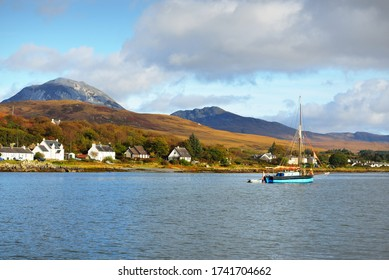 Traditional English gaff cutter with a motorboat sailing near the shore of a small town Craighouse. Mountain peaks of Paps of Jura in the background. Dramatic sky. Inner Hebrides, Scotland, UK