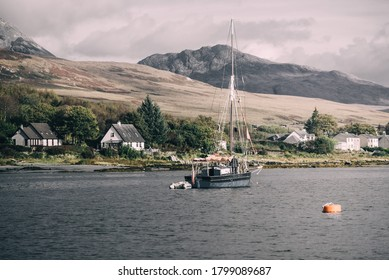 Traditional English gaff cutter with a motorboat sailing near the shore of a small town Craighouse. Mountains peaks of Paps of Jura in the background. Dramatic sky. Inner Hebrides, Scotland, UK