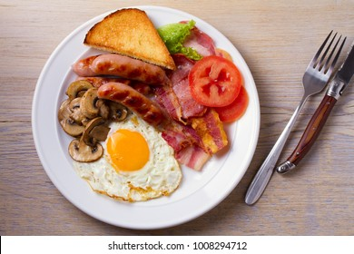 Traditional English or Irish breakfast: sausages, bacon, egg, mushrooms, tomatoes and toasts. Nutritious morning meal. View from above, top, horizontal