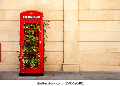 Traditional English red telephone in the city of Bath, UK, the booths were made of a garden where you can see beautiful red flowers.