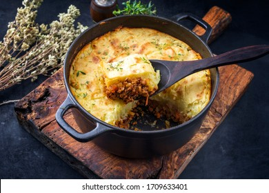 Traditioneller englischer Hirtenkuchen, der in einem niederländischen Ofen auf Holzbrett angeboten wird