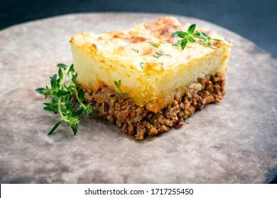 Tarte traditionnelle anglaise au berger offerte en gros plan dans une assiette au design moderne et rustique