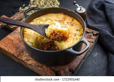 Traditional English shepherd pie offered as closeup in a Dutch oven on a wooden board