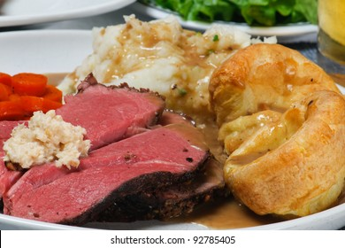 Traditional English Sunday Dinner of Roast Beef, Mashed Potatoes, Gravy, Yorkshire Pudding, Carrots, and salad.