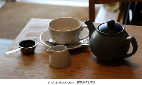 Traditional English tea set  comprising pot, cup, saucer, spoon, strainer with rest and milk jug. On wooden table.