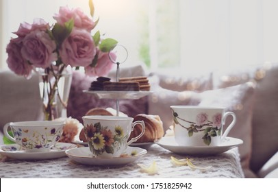 Traditional English tea time, Afternoon tea ceremony with cuppa tea, croissants, crackers and biscuits on hight tea stand in pink pastel. Cozy sence of afternoon party in conservatory room