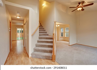 Traditional entry way with stairs and carpet.