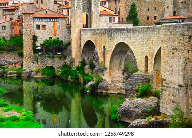 Traditional european cityscape - romanesque bridge with arches and defense towers over Fluvia river, and ancient houses dates back to the Middle Ages in Besalu, Girona, Catalonia, Spain, South Europe