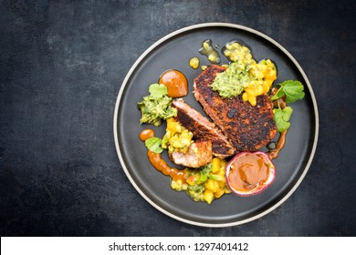 Traditional exotically blackened Cajun style tuna fish fillet with mango avocado salad, chimichurri dip and spicy BBQ sauce as top view in a modern design plate with copy space left