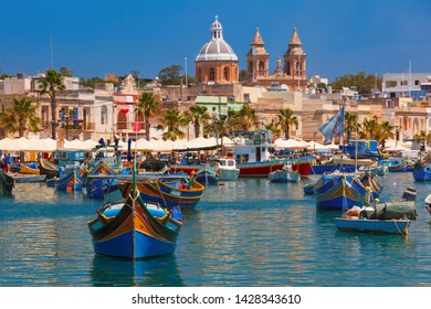 Traditional eyed colorful boats Luzzu and Parish Church of Our Lady of Pompei in the Harbor of Mediterranean fishing village Marsaxlokk, Malta