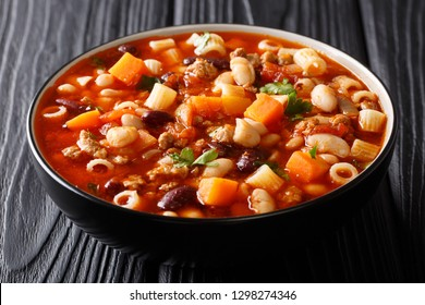 Traditional fagioli soup with vegetables, ditalini pasta and ground beef closeup in a bowl on a wooden table. horizontal