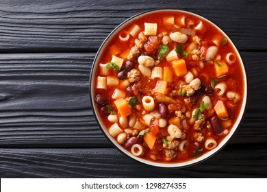 Traditional fagioli soup with vegetables, ditalini pasta and ground beef closeup in a bowl on a wooden table. horizontal top view from above
