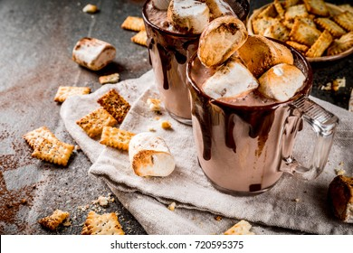 Traditional fall and winter cocktails, alcohol. Campfire hot chocolate eggnog cocktail with salted crackers and roasted marshmallow, in two mugs, on black stone table, copy space