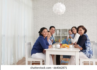 Traditional family values: portrait of big Asian family gathering at dinner table and looking at camera, smiling