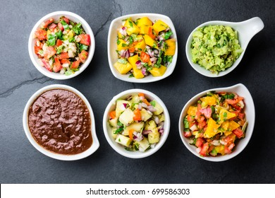 Traditional famous mexican sauces chocolate chili mole poblano, pico de gallo, avocado guacamole, salsa bandera, pinapple salsa, mango salsa on slate gray background.