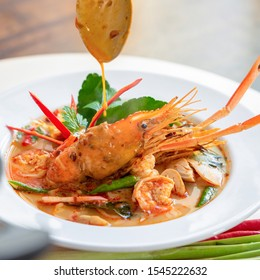 Traditional famous Thai food Tom Yum Kung or hot and spicy prawn soup with mixed herb ingredients in a bowl
