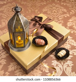 Traditional fanoos or an Arabic decorative lantern placed on top of golden gift box along with date chocolates. Eid celebration objects and background.