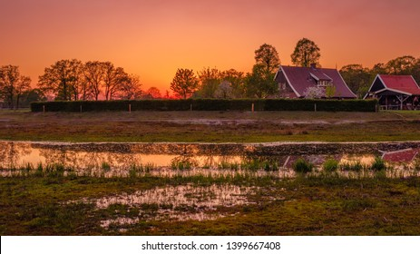 Traditional farm located along a river and ponds. The sun is setting in this Dutch farm landscape located near the small neighbourhood called Tusveld near the town of Almelo in the Eastern Netherlands