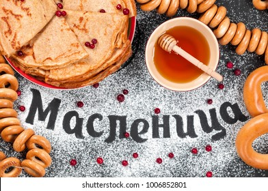 Traditional festival meal. Pancakes blini with honey and fresh cream cheese on dark background. Lettering food typography russian phrase Maslenitsa (Butter Week) spelling with sugar powder. Top view.