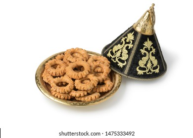 Traditional festive Moroccan tagine with Kaak cookies anise cookies isolated on white background