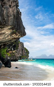 Traditional filipino banca boat on the turquoise waters of the pristine beach of Entalula island in El nido region of Palawan in the Philippines. Vertical view.