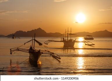 Traditional filippino boats at El Nido bay in sunset lights. Palawan island, Philippines