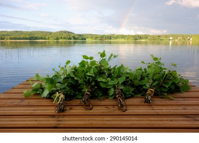 Traditional Finnish bath whisks made out of fresh birch leaves and twigs on a wet jetty by the lake on Midsummer Eve in Nokia, Finland with rainbow visible in the horizon.